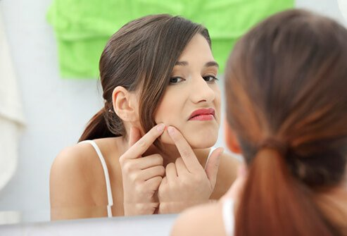 A teenage girl checks her skin in the mirror.