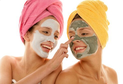 Two teenage girls apply facial moisturizers..