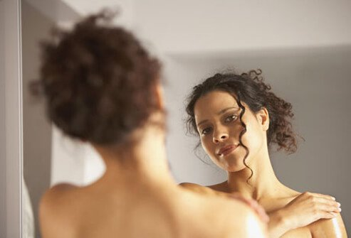A woman examines her skin in the mirror after a shower.
