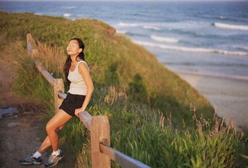 A woman resting on a beach trail after exercising to sleep better.