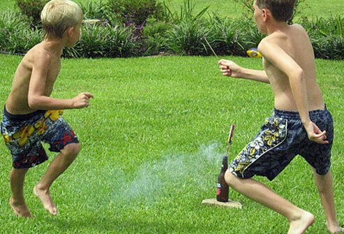 Two boys setting off firecrackers in summer.