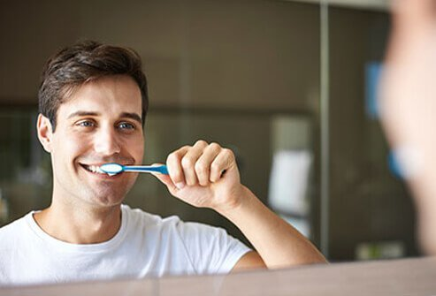 A man brushes his teeth with whitening toothpaste.