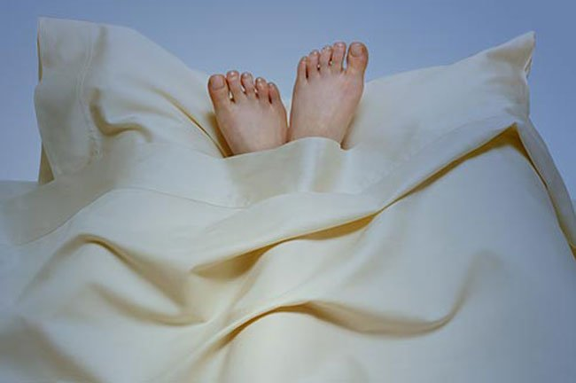 Apply a moisturizing shea butter cream or a healing ointment on your hands and feet before bed.