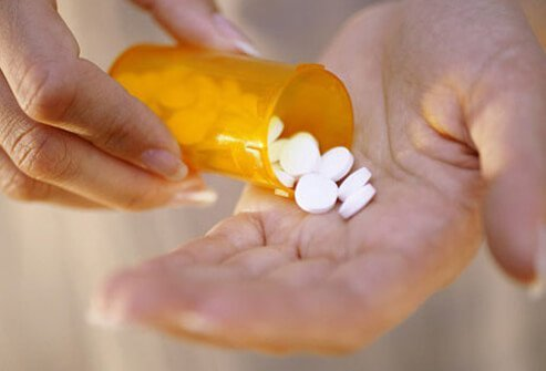 A woman takes pills from medication bottle to treat her hypothyroidism.