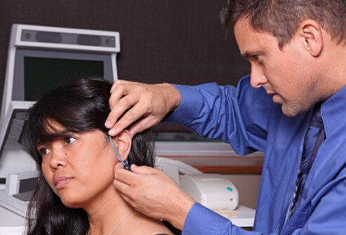 A doctor examines the ear of a female patient who suffers from tinnitus.