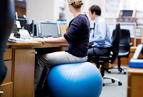 Photo of woman sitting at her desk on a posture enhancing ball.