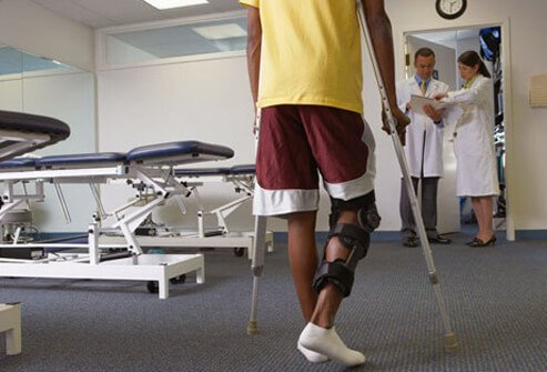 Photo of a man with a knee brace and crutches.