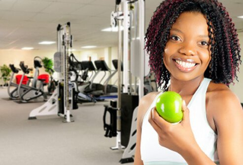 A woman enjoys a healthy snack at the gym.