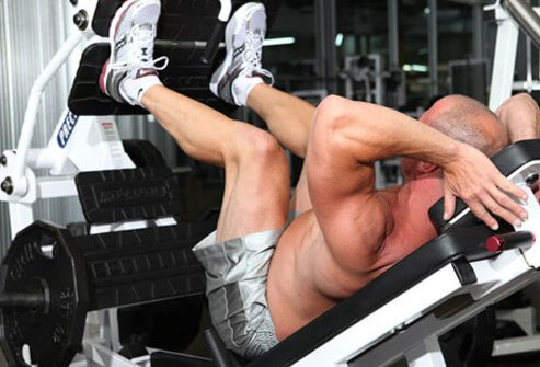 Photo of a man doing a leg press.