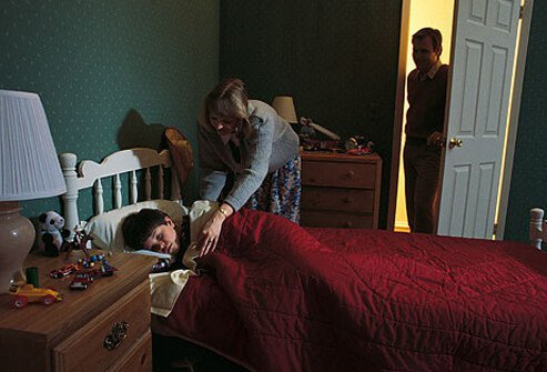 Photo of mother tucking son into pleasant bed.