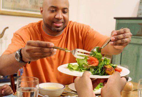 Photo of a man serving salad, managing his diabetes.