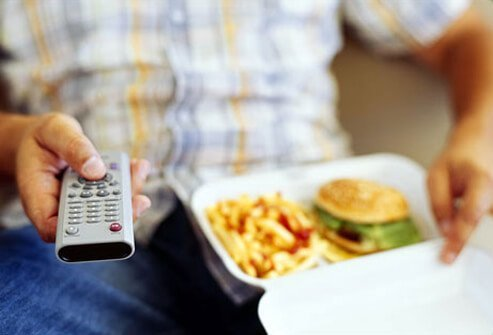 Photo of man watching TV, eating junk food.