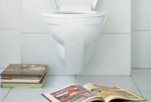 A toilet with books on the floor.