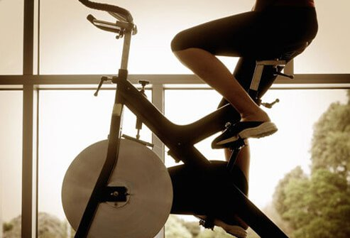 Woman riding an exercise bike.