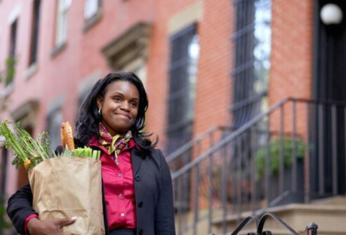 Photo of woman with lupus holding groceries.
