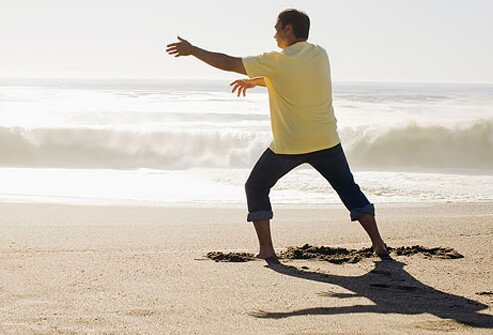 A man doing tai chi on the beach.