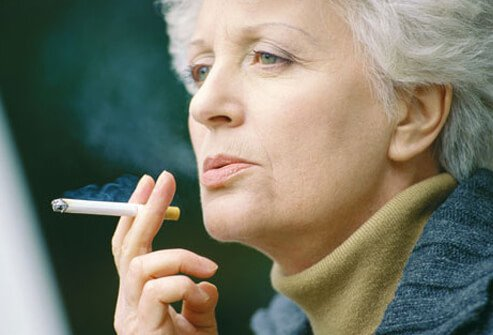 An older woman smoking, increasing her risk of stroke.