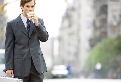 A man eating a sandwich while walking to work.
